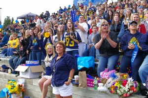 Fans wear blue and gold while screaming in support of the football team.