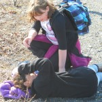 A girl coaxes her friend to keep hiking after a short break spent on the ground.