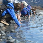 The class is instructed to test the temperature of glacial water so they'll think twice before wading in.